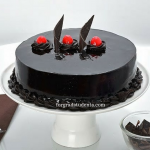 Picture of rich dark chocolate cate with 3 cherries on top