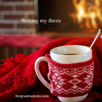 Coffee cup on table with red blanket and fireplace in background. Writing my thesis
